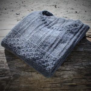 The Skye sweater sitting on driftwood
